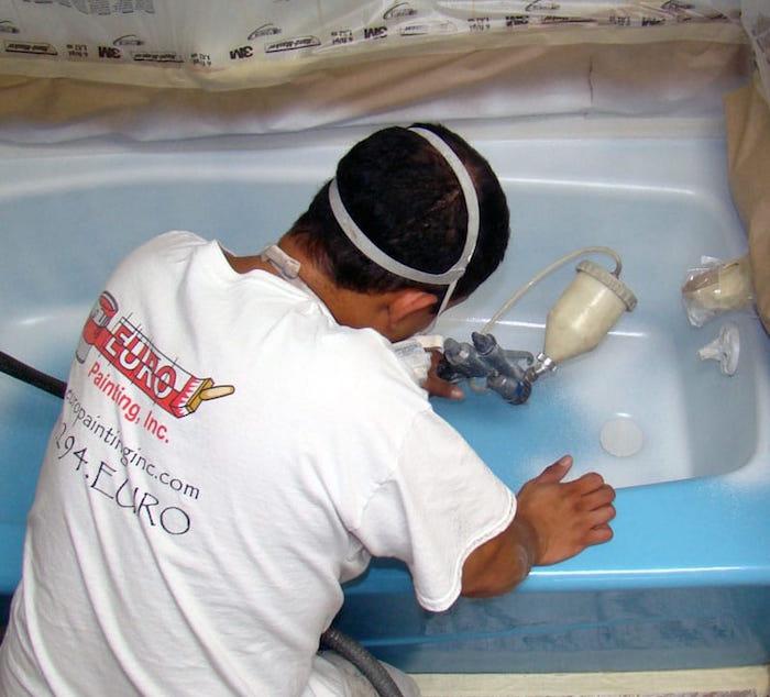 peintre appliquant de la peinture pour baignoire epoxy au pistolet pour rénovation de salle de bain