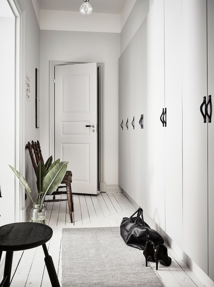 couloir de style scandinave aux murs blancs avec des touches de noir sur le mobilier, meuble couloir entrée avec rangements intégrés