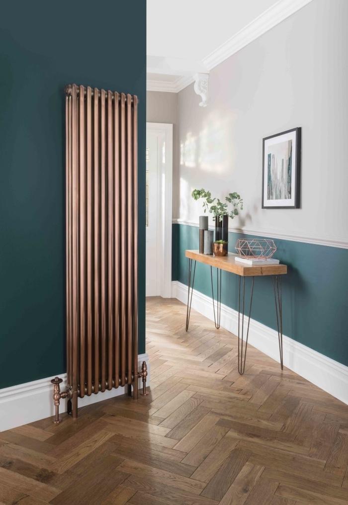 la peinture bleu canard sur le bas du mur et le mur adjacent s'associe avec le bois et le radiateur à finition en cuivre pour apporter une note d'élégance au couloir