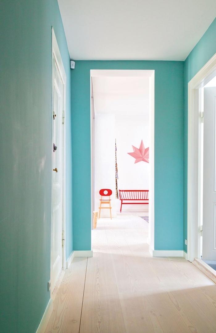 le bleu turquoise des murs s'harmonise parfaitement avec les portes blanches et le parquet clair pour créer une ambiance moderne et apaisante dans le couloir