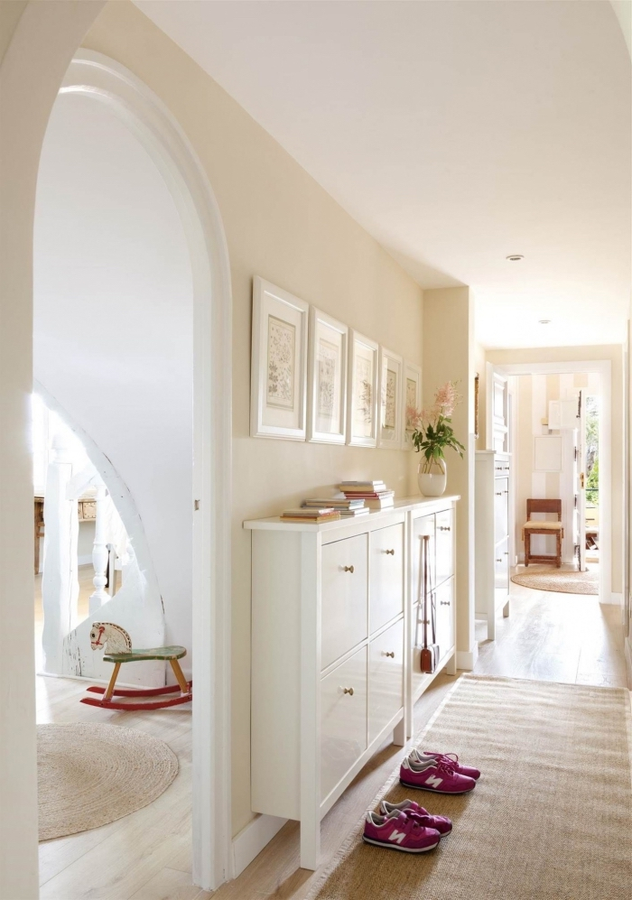 le blanc cassé sur les murs du couloir dominé par des tons neutres illumine l'espace et crée une ambiance apaisante