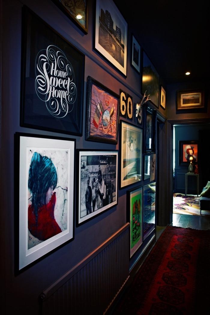 peinture couleur bleu nuit sur les mur d'un couloir aménagé comme une véritable galerie avec de nombreux cadres photos