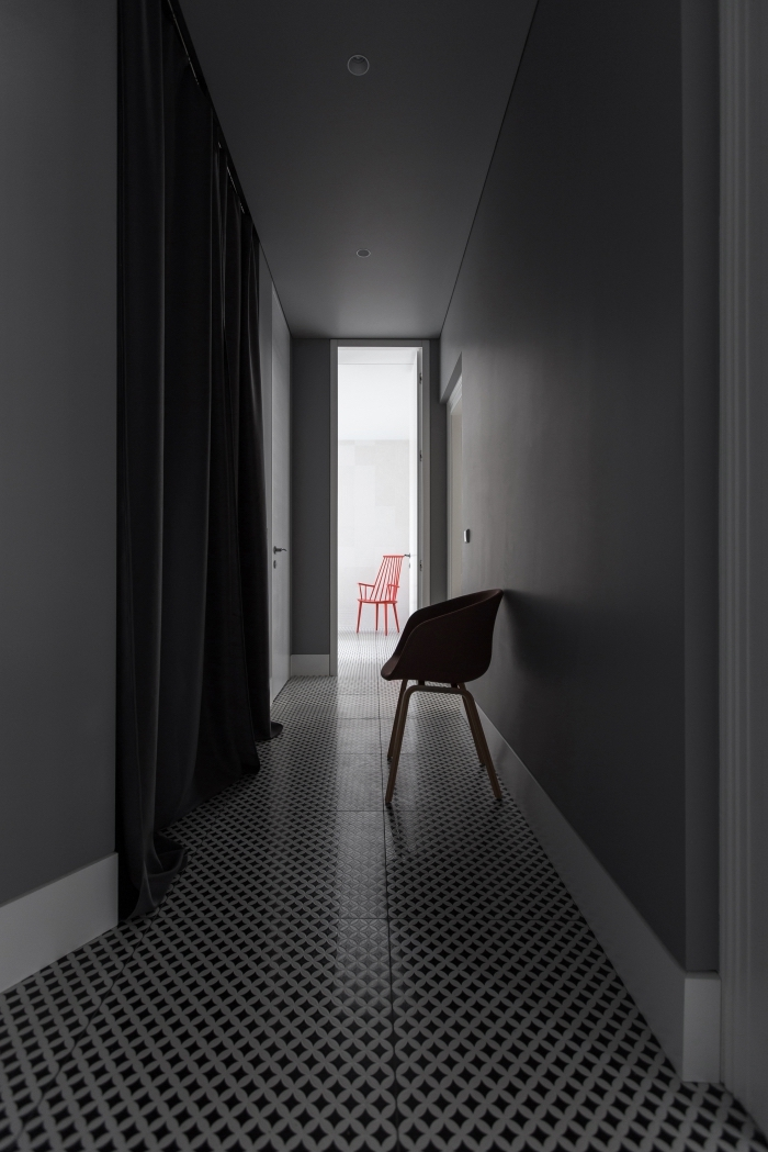 decoration couloir long et étroit sobre et sophistiqué au sol en vinyle graphique noir et blanc qui donne sur une pièce à vivre blanche