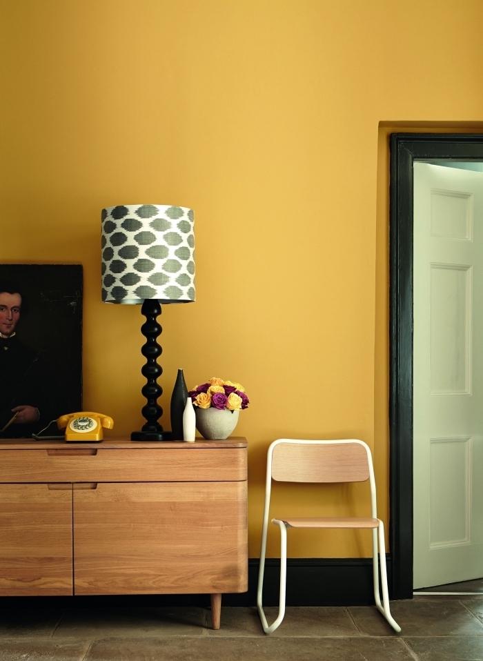 idée deco jaune moutarde dans un salon aux murs jaune, meubles salon de bois clair, modèle lampe blanc et gris foncé