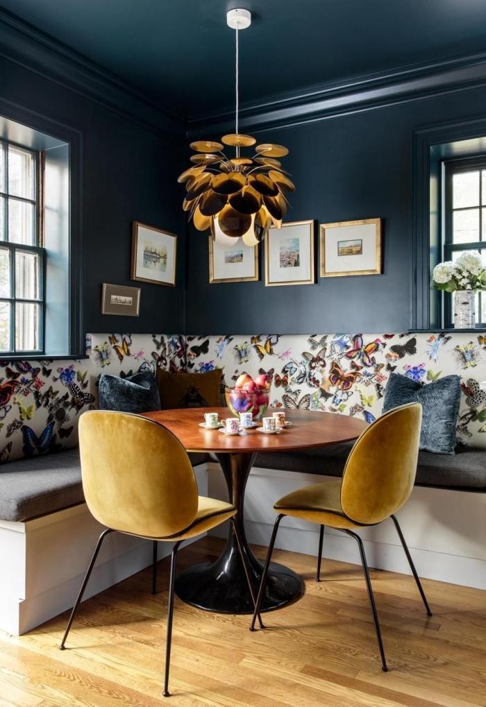 chaise métal avec siège de couleur ocre, peinture foncée pour murs dans un salon ou salle à séjour, lampe suspendue finition dorée
