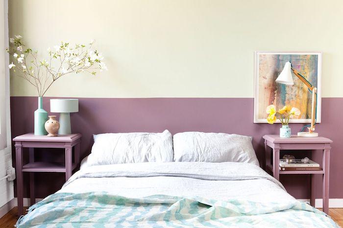 pan de mur en couleur mauve et haut de mur en jaune clair, linge de lit blanc cassé et bleu, table de nuit mauve, tableau peinture artistique
