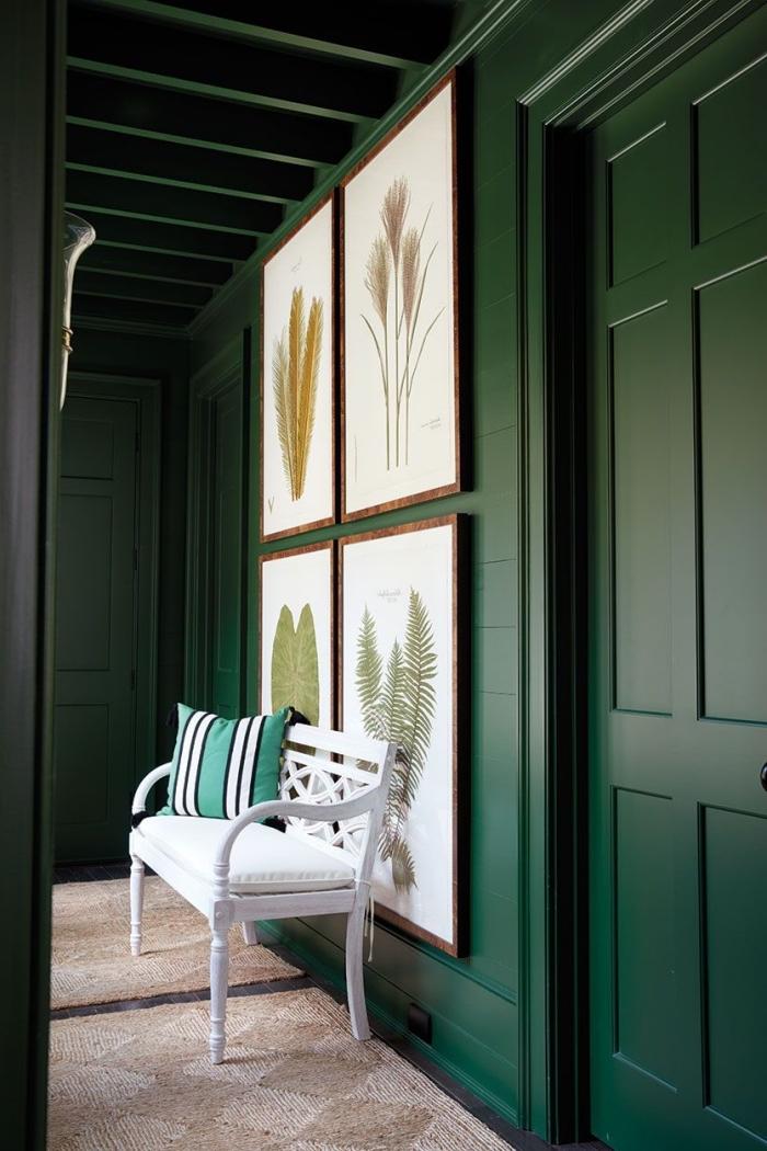 couleur couloir vert sapin profond illuminé par des touches de blanc dans les affiches encadrées