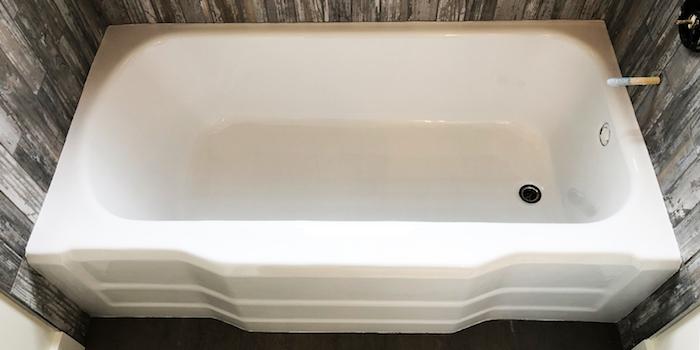 baignoire rénovée avec nouvelle peinture epoxy blanche et mur avec revêtement imitation bois gris