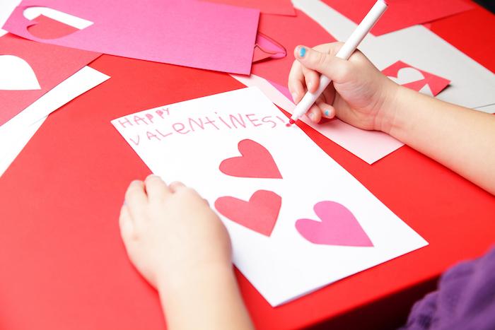 activité manuelle primaire, carte de saint valentin dans papier blanc avec des coeurs en papier collés dessus et texte d amour