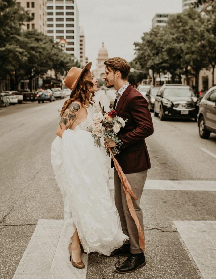 robe de mariée chic, chapeau feutre, veste homme bordeaux, bouquet de roses, tatouage femme, tenue de mariage vintage