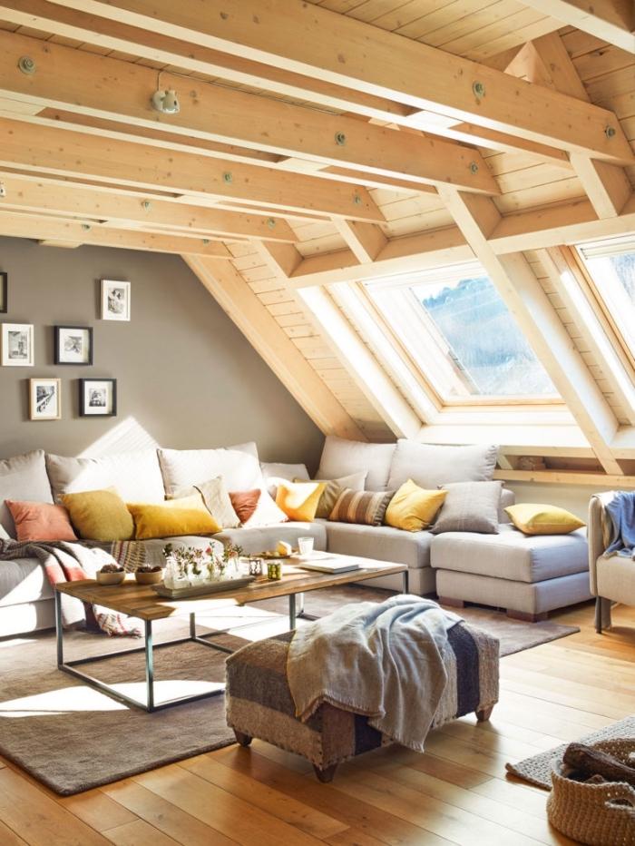 exemple comment aménager une pièce sous combles avec plafond en poutres bois, mur de cadres photos en noir et bois