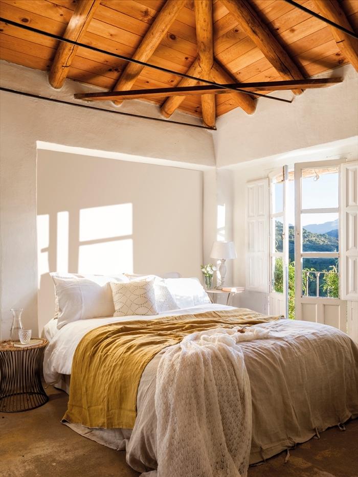 accents jaune moutarde dans une pièce blanche de style rustique, déco chambre à coucher avec plafond bois foncé