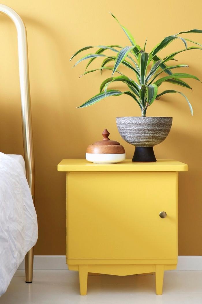 meuble de chevet moderne de couleur ocre, accessoires déco boîte à bijoux blanc et bois, chambre aux murs jaune et plancher blanc