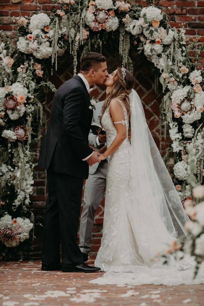 mariage traditionnel, robe longue blanche avec traine, costume marié noir, déco murale fleurs