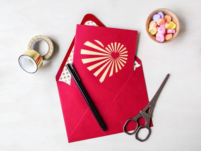 carte avec coeur sur la face, coeur en bandes de papier jaune pale sur fond rouge rangée dans une enveloppe rouge