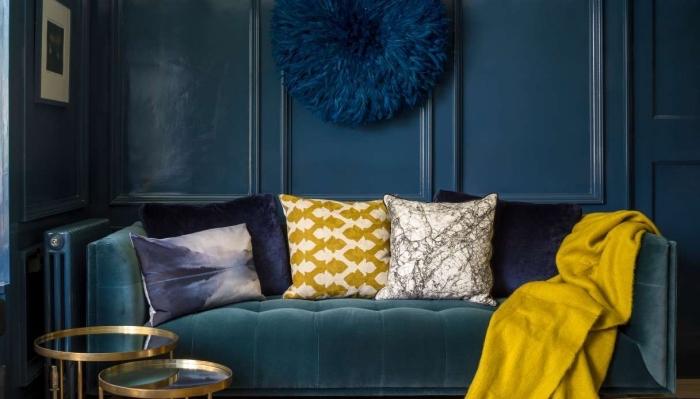 salon foncé avec canapé en velours, modèle de suspension murale bleu marine, accessoires de couleur moutarde