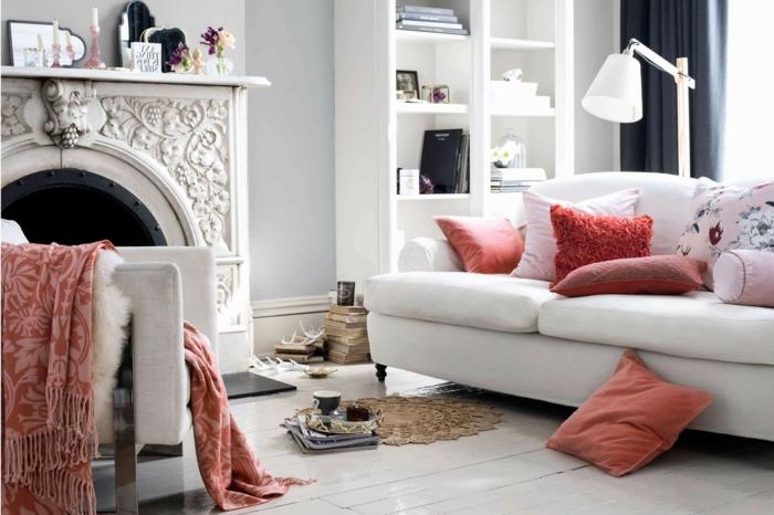 grande cheminée en gris clair, fauteuil gris, couverture fourrure blanche et jeté rose doux, sol en planches, coussins corail, lampe de sol blanche, étagère blanche
