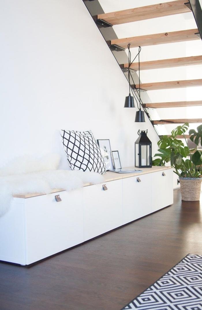 un module de rangement besta sous l'escalier qui joue le rôle de banquette ikea de style scandinave