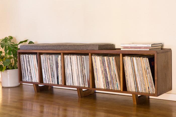 meuble en bois bas et large avec casiers pour rangement vinyles pouvant servir de banc avec coussin