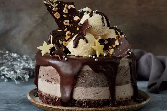 gateau nutella glacé au glaçage chocolat décadent, garni de boules de glace et de copeaux de chocolat