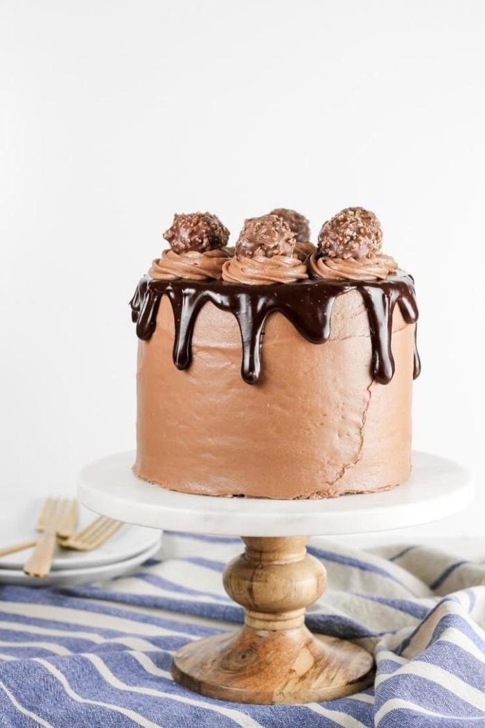 idée de gateau anniversaire adulte de plusieurs étages au chocolat et au glaçage de fromage frais et nutella décoré de truffes aux éclats de noisettes