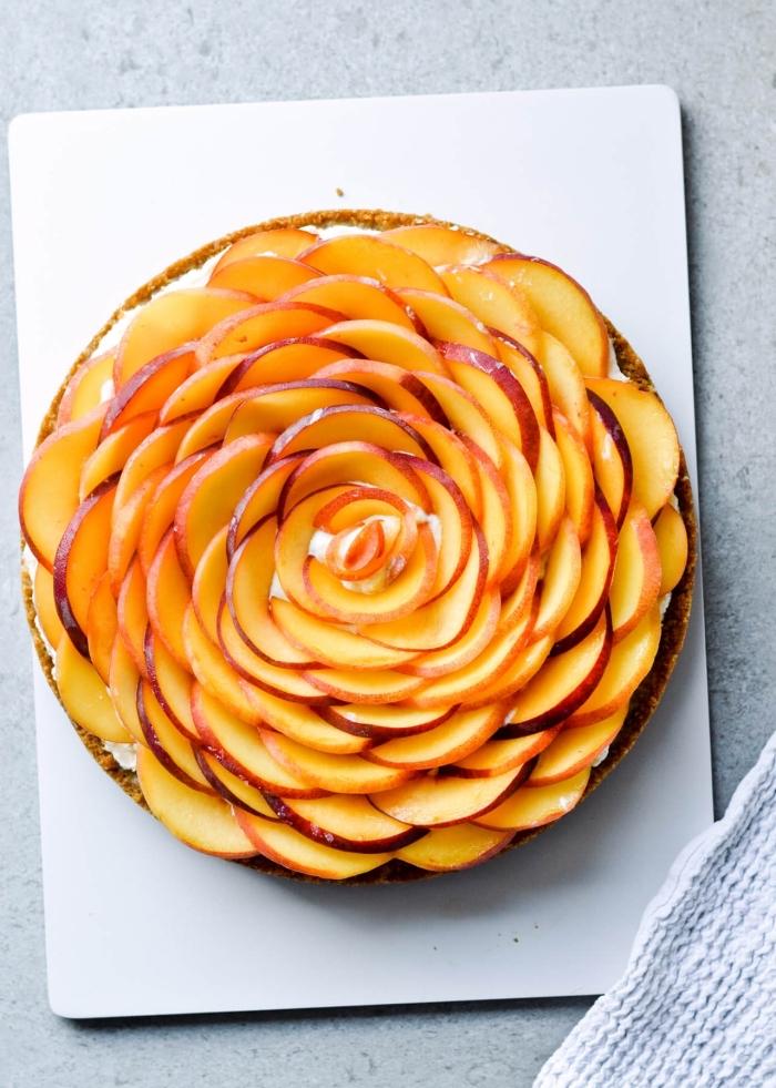 tarte aux pêches et au mascarpone à base de pâte sablée, décor de lamelles de pêches en forme de rose