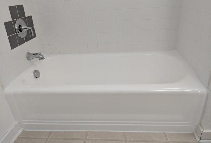 salle de bain rénovée avec nouvelle peinture et nouveaux joints de baignoire et mur en carrelage