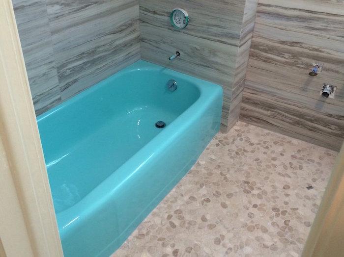 nouvelle peinture epoxy bleu turquoise après rénovation de salle de bain aux murs imitation bois