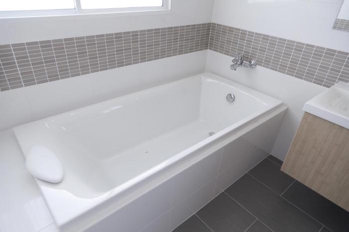 salle de bain rénovée avec credence murale et carrelage au sol et baignoire repeinte avec peinture epoxy