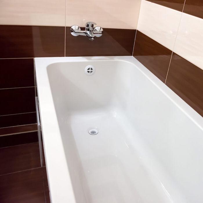 salle de bain avec carrelage mural blanc et marron et nouvelle peinture baignoire blanche