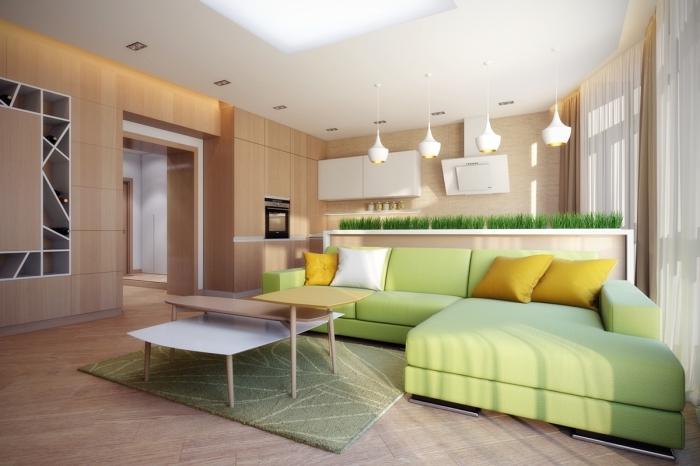 déco de salon aux murs bois ouvert vers la cuisine, modèle de canapé d'angle de couleur vert amande avec coussins moutarde
