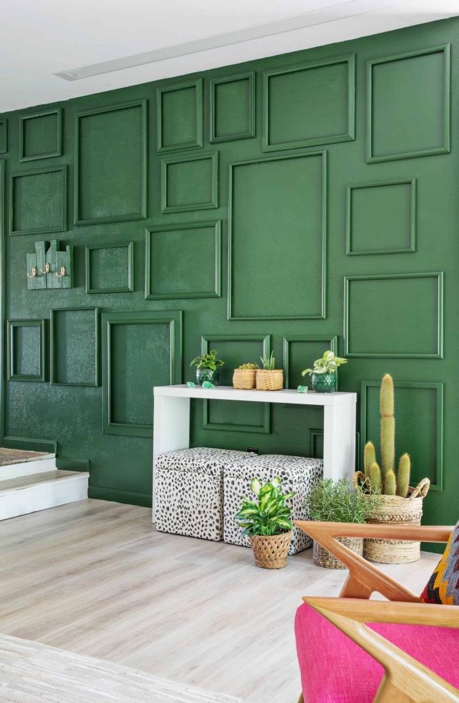 décoration murale originale avec peinture de couleur vert sapin et cadres, pièce au plafond blanc et plancher bois clair