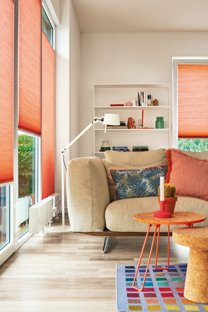 rideaux couleur pêche, étagère blanche, lampe de sol blanche, grand sofa beige, petite table ronde et tabouret en bois, coussins, tapis multicolore