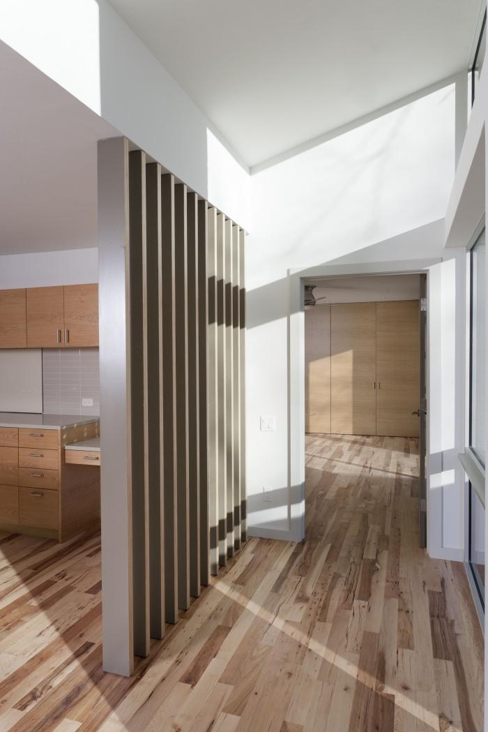 design intérieur moderne dans une cuisine ouverte aux murs blancs avec plancher et meubles en bois