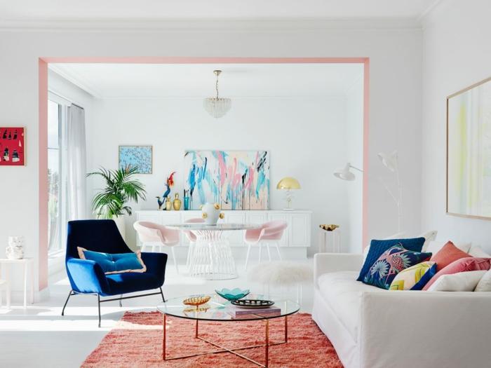 intérieur blanc aux accents pétillants, tapis couleur corail, sofa blanc et coussins déco, fauteuil bleu, tableau peinture abstraite, table avec deux chaises roses