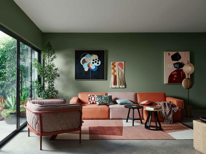 tapis patchwork, mur vitré, fauteuil gris, deux petites tables de salon, tableaux peintures abstraites, peinture murale vert