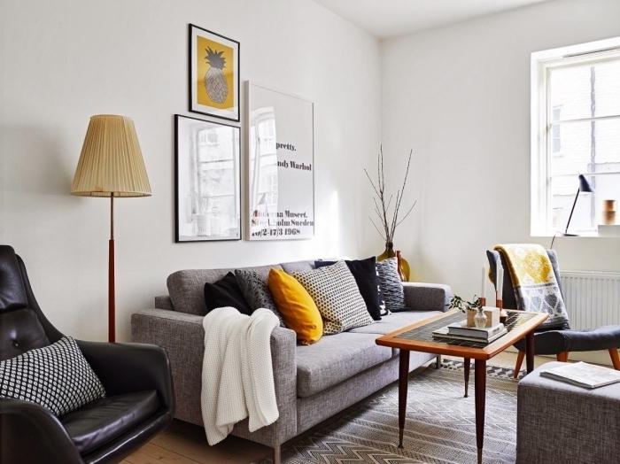 idée mur de cadres noir et blanc dans un salon cozy, modèle fauteuil cuir noir avec coussin gris et noir, objet deco jaune