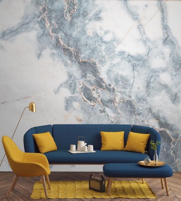 design intérieur moderne, décoration salon aux murs à effet marbre aux accents cuivrés, modèle de canapé bleu marine avec objet déco moutarde