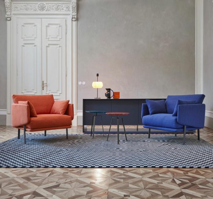 grande porte blanche, deux fauteuils confortables, deux petites tables basses, tapis motif mosaique, mur gris béton