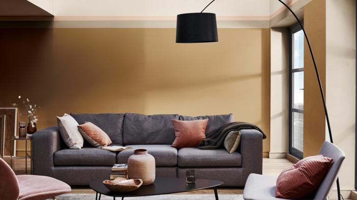 mur couleur marron, sofa gris, coussins terracotta, table basse asymétrique, chaises élégantes, grand lampadaire noir