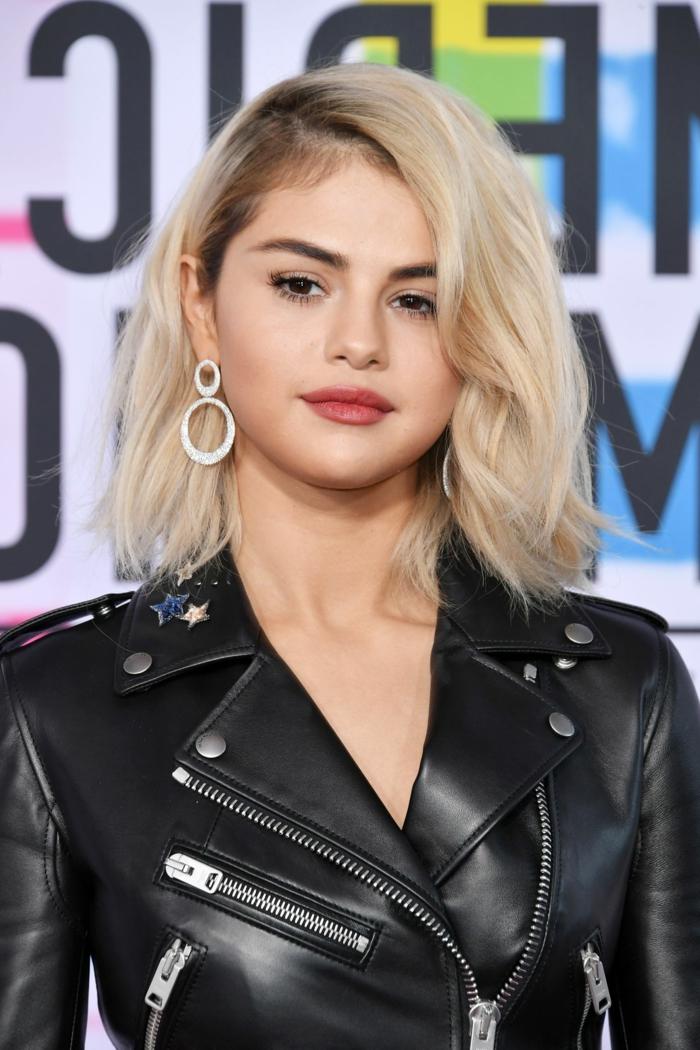 Blonde selena gomez avec une veste moto, coupe de cheveux mi long dégradé, modernes coiffures tendnance 2019
