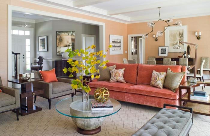 grand sofa en couleur corail, banquette capitonnée, table ronde en verre, coussins beiges, lampe molécules, peinture murale pêche