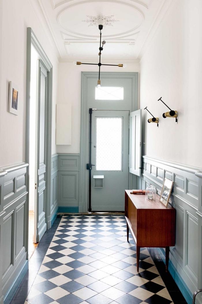 la teinte douce du vert sauge sur les boiserie associée au blanc des murs confère au couloir vintage une ambiance apaisante et accueillante, couloir d'entrée avec carrelage damier noir et blanc au sol