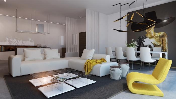 design intérieur moderne dans un studio, déco salon ouvert vers salle à manger au plancher gris et murs blancs avec objets de déco moutarde