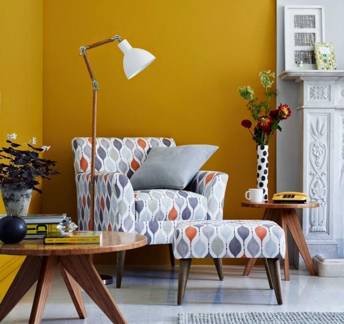 déco de salon aux murs de peinture jaune moutarde avec cheminée blanche, modèle table basse ronde bois foncé