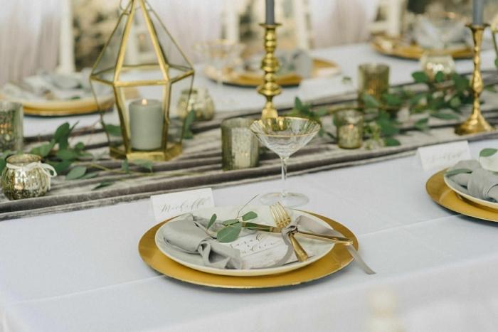 deco table mariage, chemin de table gris, sous-assiettes dorés, assiettes blanches, bougeoirs en verre et métal doré,