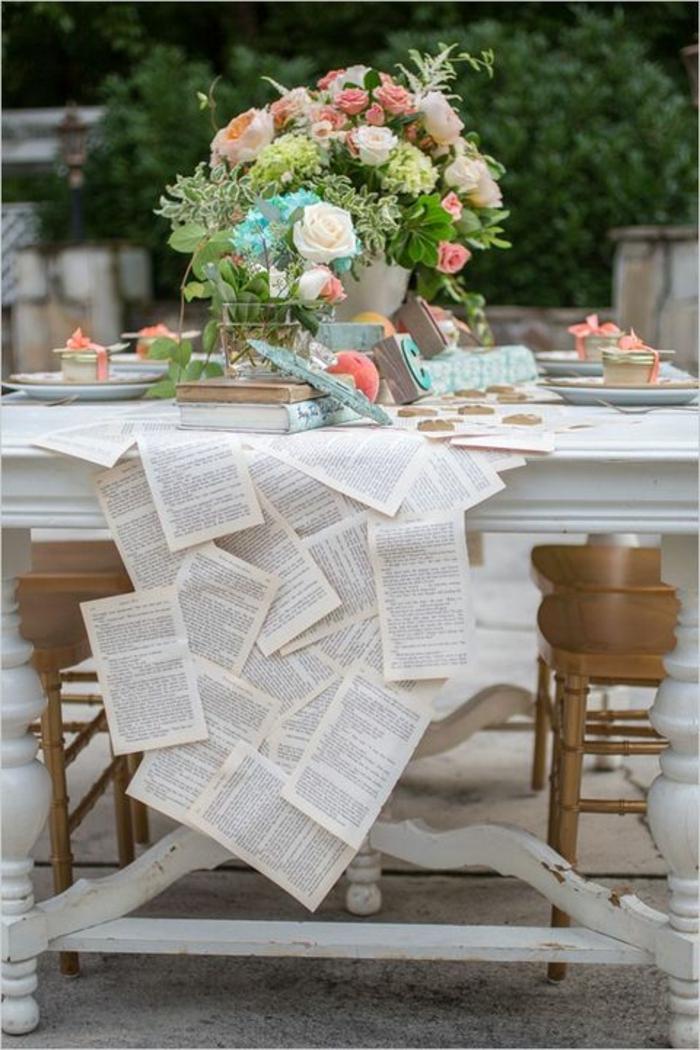 decoration table mariage originale, plusieurs feuilles de livre attachées, grand bouquet multicolore de roses, table blanche