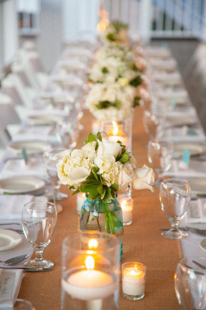 toile de jute passant par la table de mariage, bocaux de verre pleins de roses crème, verres à vin