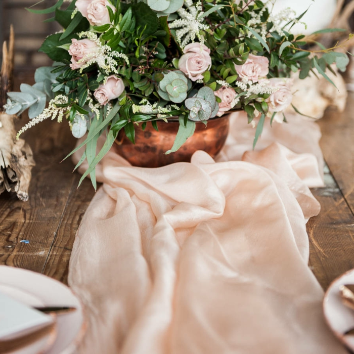 grand bol couleur cuivré avec bouquet de roses et feuillage, chemin de table rose, table en bois brut