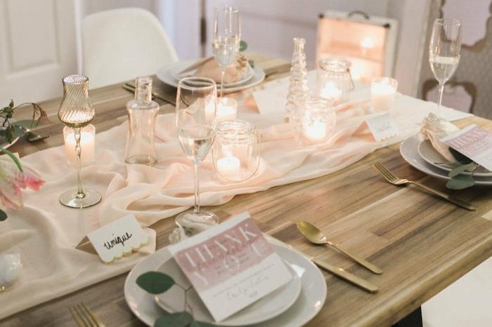 table en bois, assiettes blanches, chemin de table rose, verres élégants, chaises blanches, ustensiles dorées